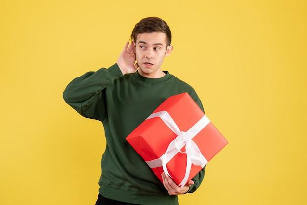 Vue de face jeune homme avec pull vert écoutant quelque chose tenant cadeau sur jaune