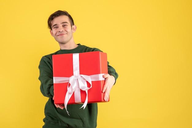 Vue de face jeune homme avec pull vert montrant son cadeau sur jaune