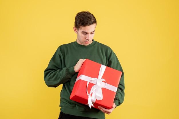 Vue de face jeune homme avec pull vert regardant cadeau sur jaune