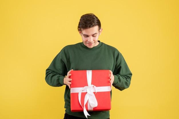 Vue de face jeune homme avec pull vert en regardant son cadeau sur jaune