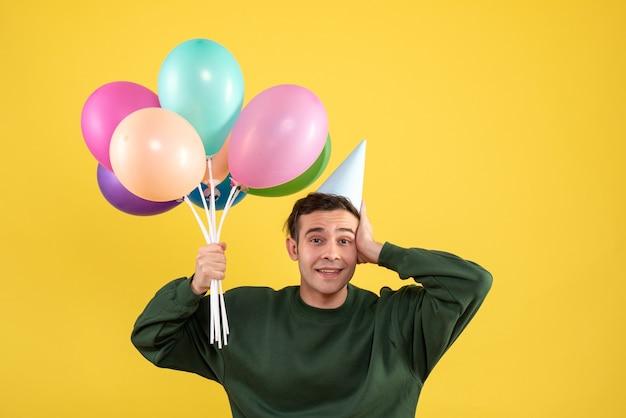 Vue de face jeune homme avec pull vert tenant des ballons debout sur jaune