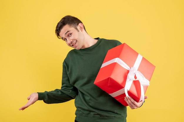 Vue de face jeune homme avec pull vert tenant cadeau sur jaune
