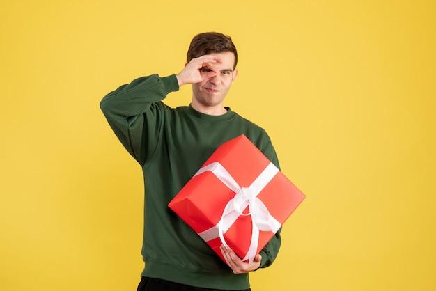 Vue de face jeune homme avec pull vert tenant un cadeau de noël sur jaune