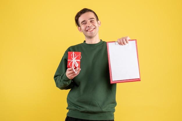 Vue de face jeune homme avec pull vert tenant cadeau et presse-papiers debout sur jaune