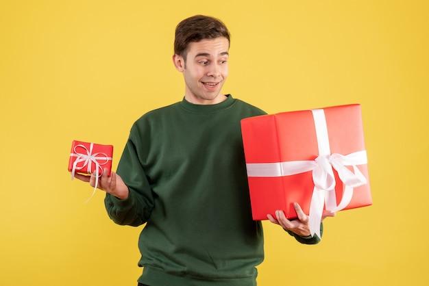 Vue de face jeune homme avec pull vert tenant des cadeaux debout sur jaune