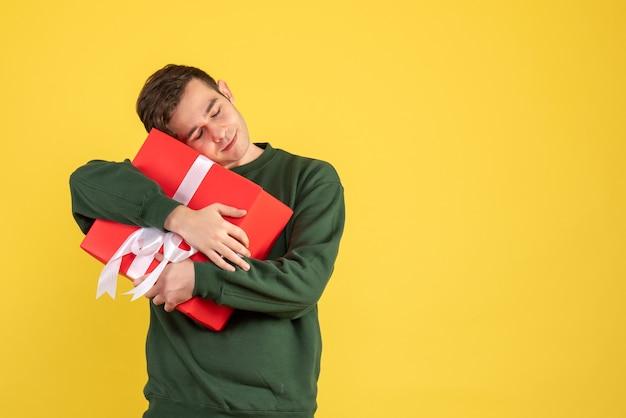 Vue de face jeune homme avec pull vert tenant fermement son cadeau sur jaune