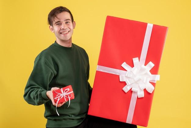 Vue de face jeune homme avec pull vert tenant de grands et petits cadeaux debout sur jaune