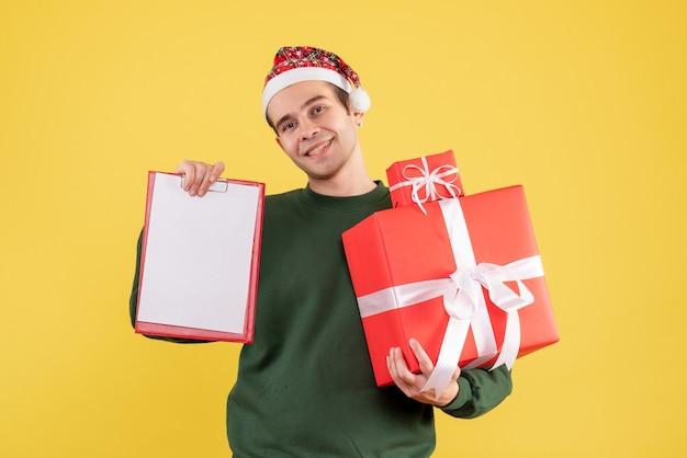 Vue de face jeune homme avec pull vert tenant gros cadeau et presse-papiers debout sur jaune