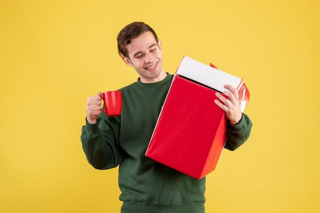Vue de face jeune homme avec pull vert tenant gros cadeau et tasse rouge debout sur jaune