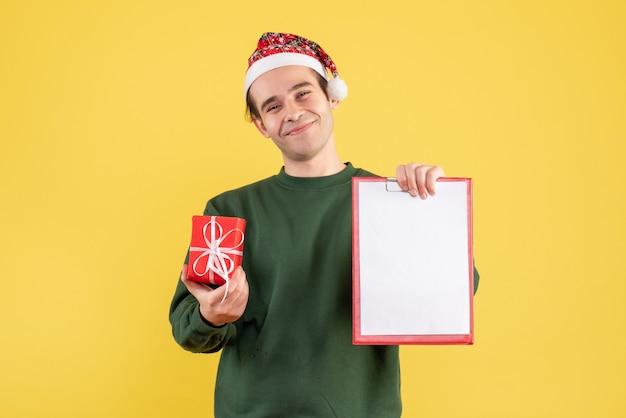 Vue de face jeune homme avec pull vert tenant le presse-papiers et cadeau debout sur jaune