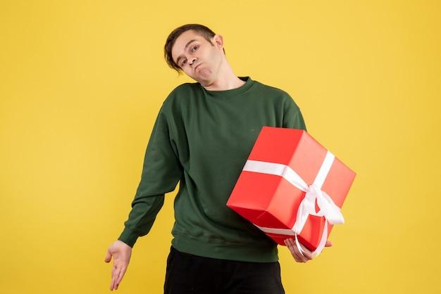 Vue de face jeune homme avec pull vert tenant son cadeau sur jaune