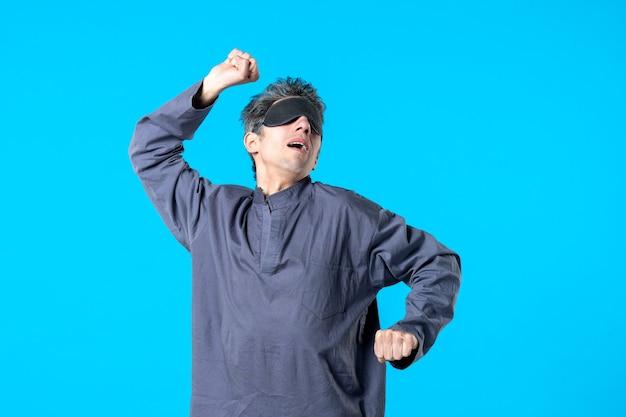 Vue de face jeune homme en pyjama et bandage de couchage bâillement sur fond bleu sommeil rêve nuit cauchemar reste sombre couleur de la chambre