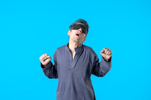 Vue de face jeune homme en pyjama avec bandage pour dormir bâillant sur fond bleu couleur sommeil rêve cauchemar nuit lit chambre sombre