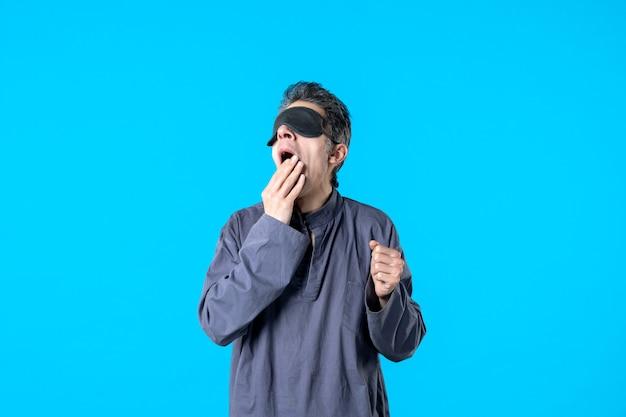 Vue de face jeune homme en pyjama avec bandage pour dormir sur fond bleu couleur sommeil rêve cauchemar nuit lit chambre bâillement sombre