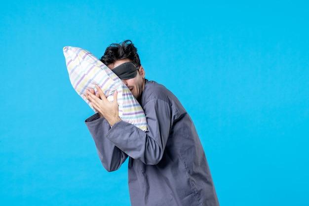 Vue de face jeune homme en pyjama et bandage pour dormir sur fond bleu nuit de sommeil de rêve fin de sillage humain repos couleur cauchemar