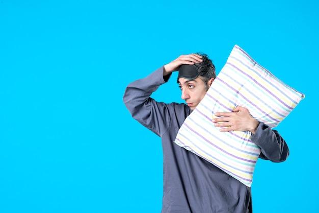Vue de face jeune homme en pyjama tenant un oreiller sur fond bleu couleur chambre reste cauchemar insomnie lit sombre sommeil rêves nuit