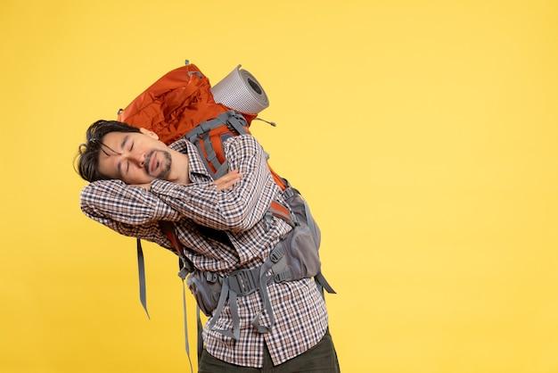 Vue de face jeune homme en randonnée avec sac à dos dormant sur jaune
