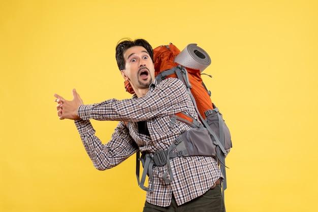 Vue de face jeune homme en randonnée avec sac à dos sur jaune