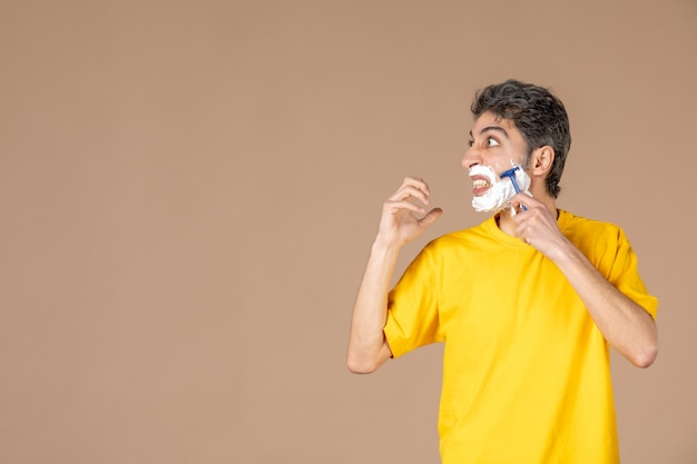 Vue de face jeune homme rasant son visage en mousse sur fond rose