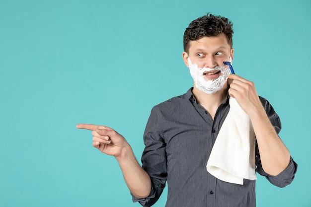 Vue de face jeune homme rasant son visage en mousse avec un rasoir sur fond bleu