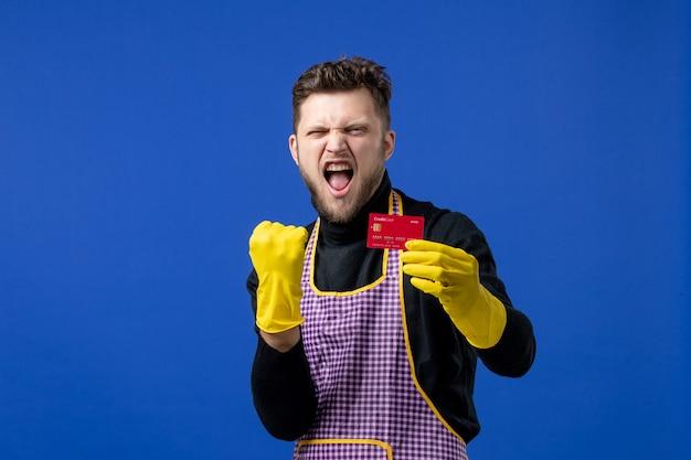 Vue de face d'un jeune homme ravi tenant une carte montrant un geste gagnant sur le mur bleu
