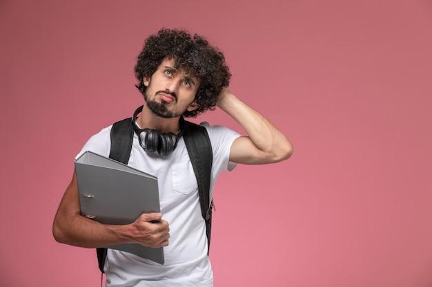 Vue de face jeune homme réfléchissant à quelque chose de nécessaire et tenant le classeur