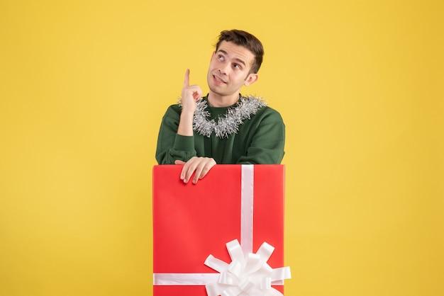 Vue de face jeune homme regardant au plafond debout derrière une grande boîte-cadeau sur jaune