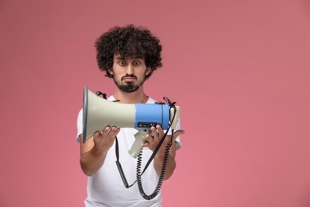 Vue de face jeune homme regardant microphone à main avec intérêt