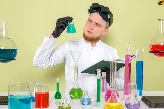 Vue de face jeune homme regardant un produit chimique bleu clair