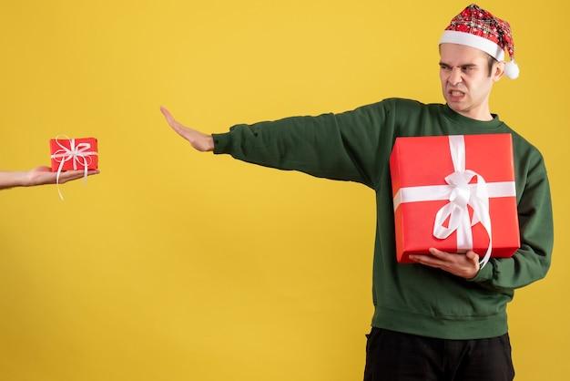 Vue de face jeune homme rejetant le cadeau en main féminine sur jaune