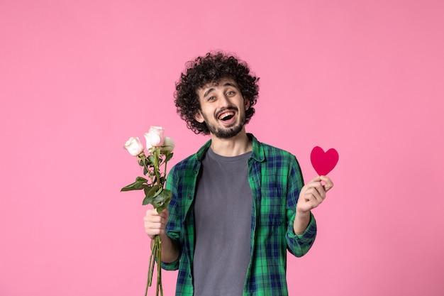 Vue de face jeune homme avec roses roses et autocollant coeur rose