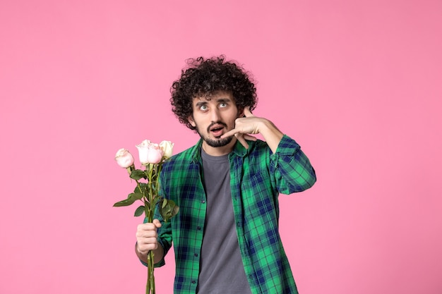 Vue de face jeune homme avec des roses roses comme cadeau pour la journée des femmes sur la couleur rose