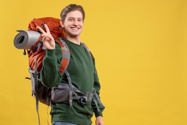 Vue de face jeune homme avec sac à dos se préparant à la randonnée souriant