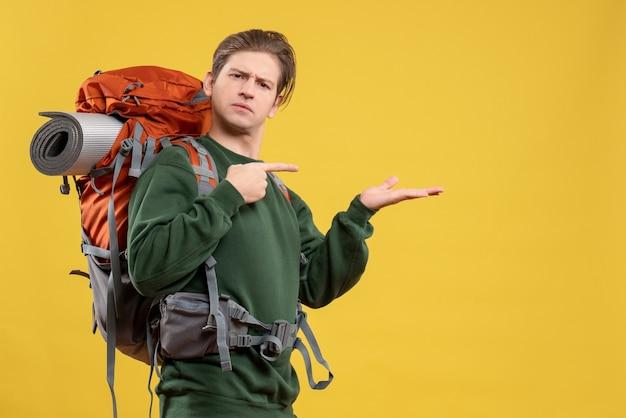 Vue de face jeune homme avec sac à dos se préparant à la randonnée