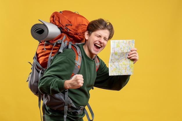 Vue de face jeune homme avec sac à dos tenant la carte