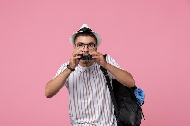 Vue de face jeune homme avec sac et jumelles sur un bureau rose