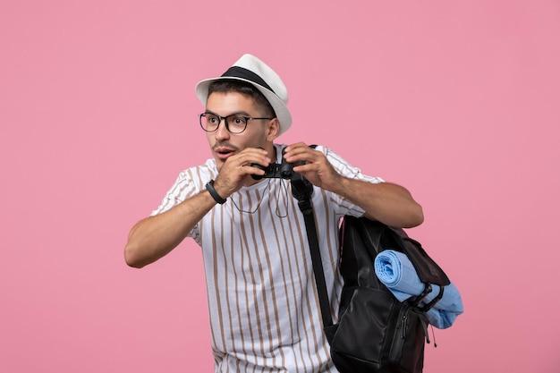 Vue de face jeune homme avec sac et jumelles sur fond rose clair