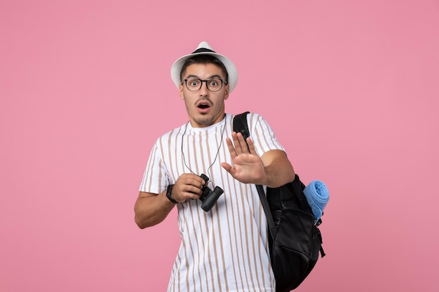 Vue de face jeune homme avec sac et jumelles sur fond rose
