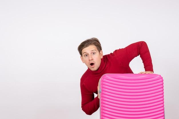 Vue de face jeune homme avec sac rose sur fond blanc