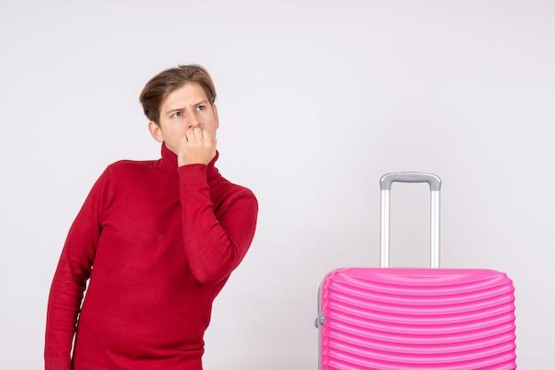 Vue de face jeune homme avec sac rose pensant sur fond blanc