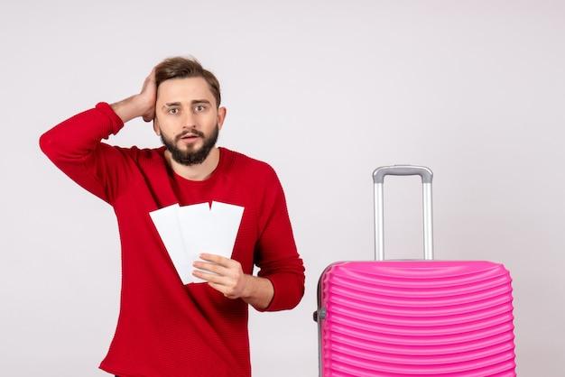 Vue de face jeune homme avec sac rose et tenant des billets sur un mur blanc voyage vol couleur voyage vacances photo émotion