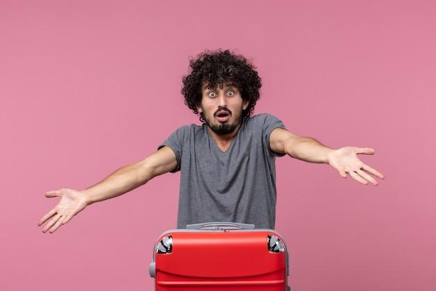 Vue de face jeune homme avec sac rouge se préparant pour un voyage sur un bureau rose