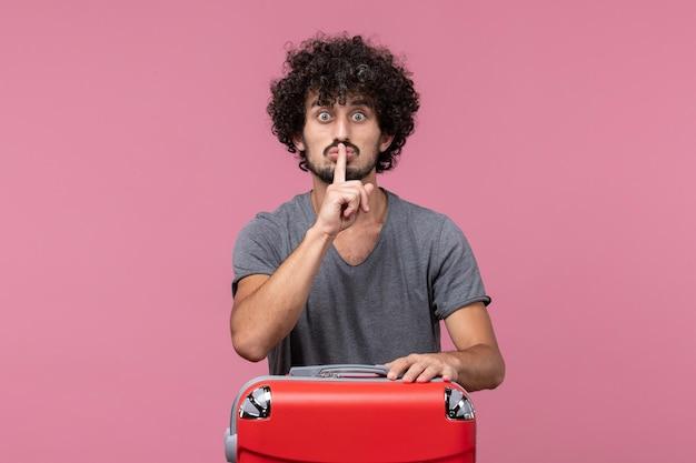 Vue de face jeune homme avec sac rouge se préparant pour un voyage sur l'espace rose