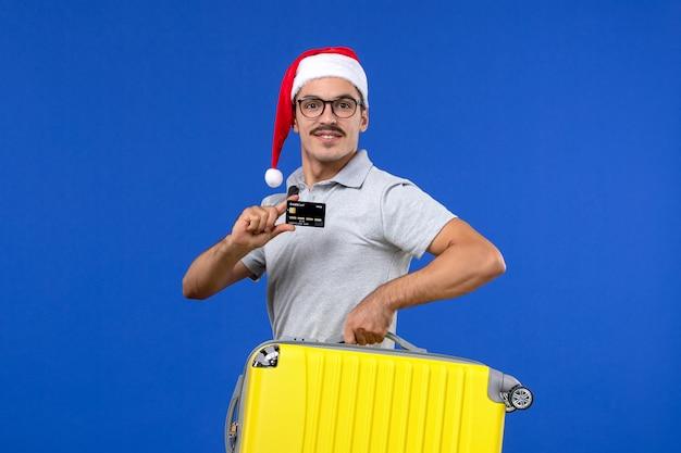 Vue de face jeune homme sac de transport et carte bancaire sur avion de vacances vol mur bleu