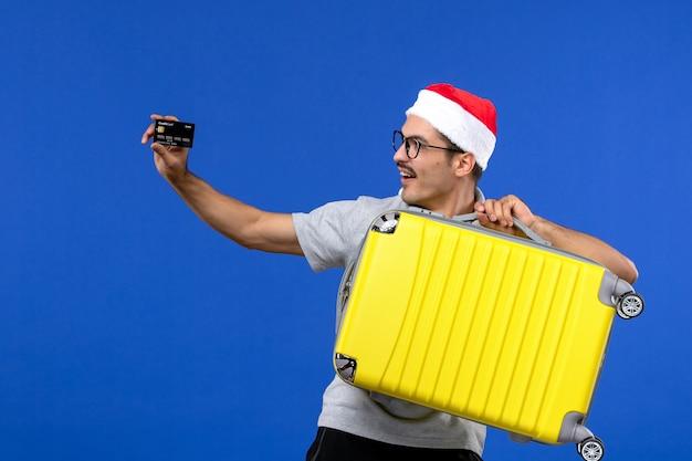 Vue de face jeune homme sac de transport et carte bancaire sur avion de vacances de vols de mur bleu