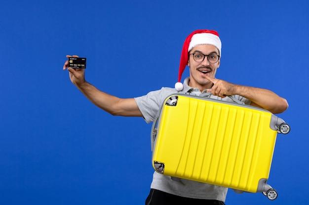 Vue de face jeune homme sac de transport et carte bancaire sur les avions de vacances de vols de mur bleu
