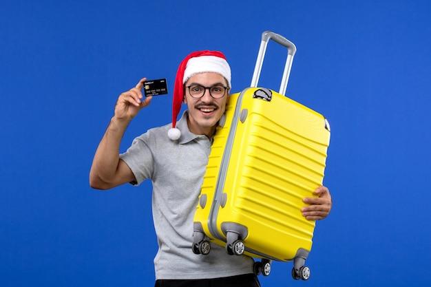 Vue de face jeune homme sac de transport et carte bancaire sur les avions de vol de vacances bureau bleu