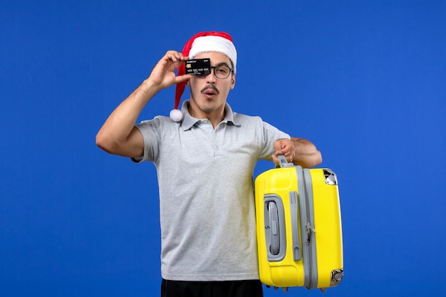 Vue de face jeune homme sac de transport et carte bancaire sur les avions de vol de vacances mur bleu