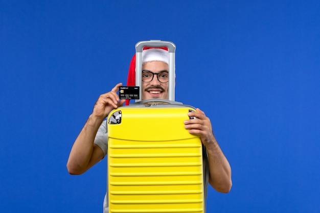 Vue de face jeune homme sac de transport et carte bancaire sur les avions de vols vacances mur bleu