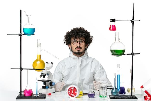 Vue de face jeune homme scientifique en costume spécial assis avec différentes solutions sur mur blanc